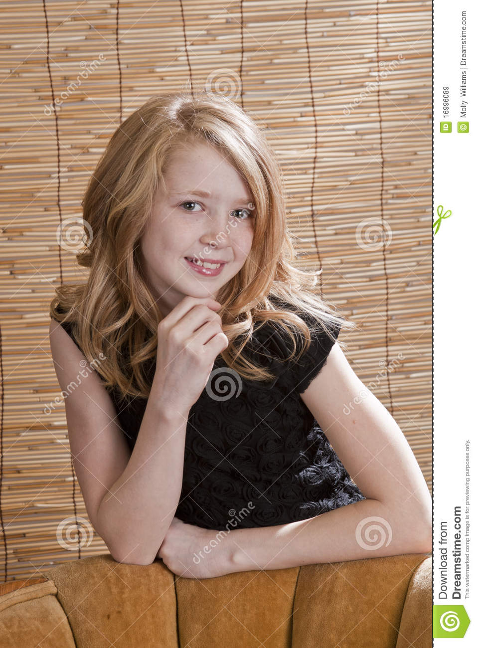 Young preteen girl looking off to the side while sitting in a chair ...