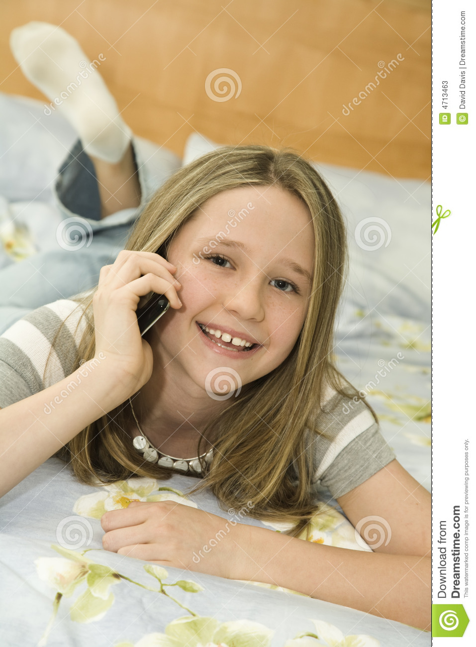 Caucasian preteen girl laying in bed talking on a cell phone.