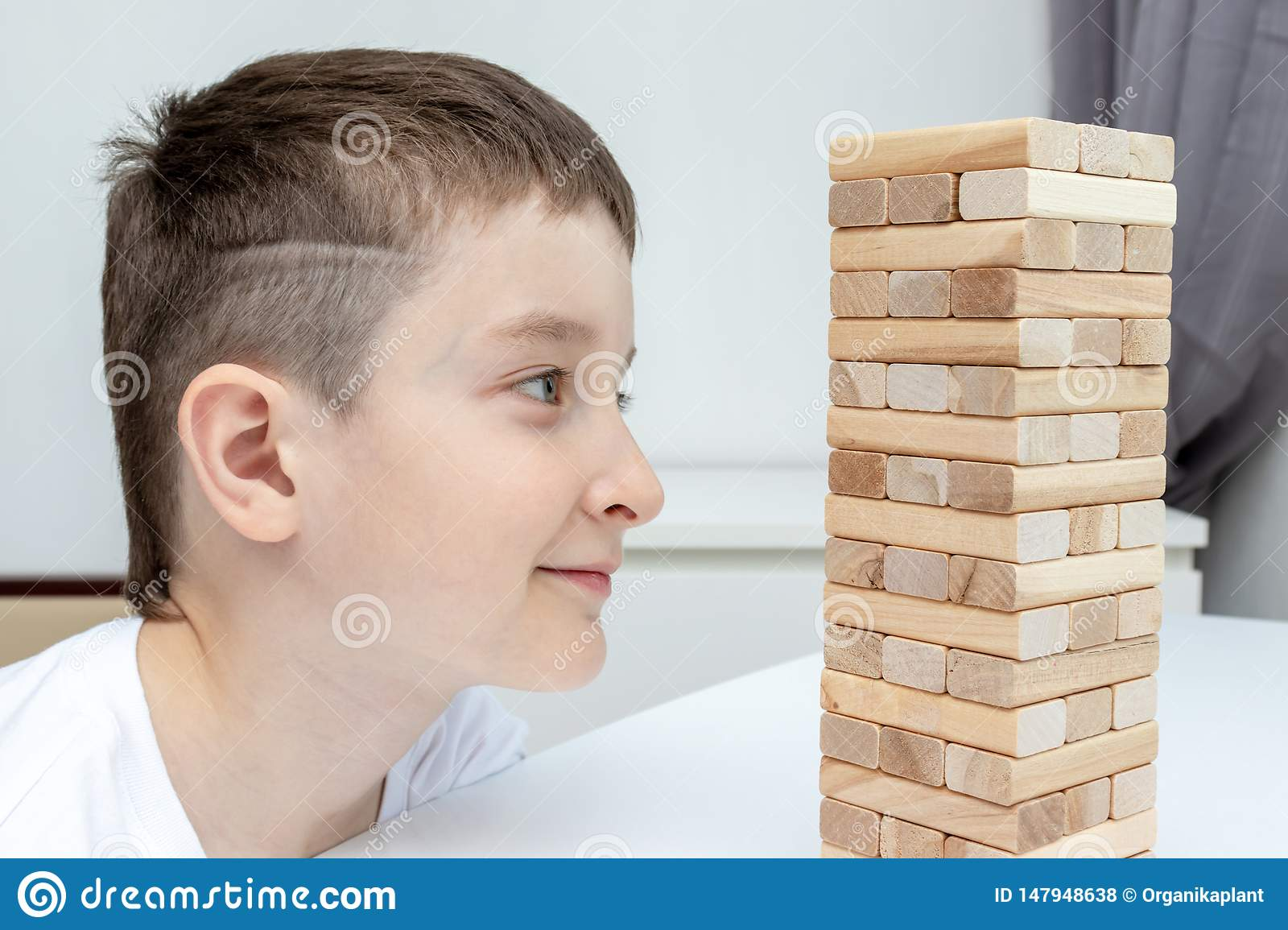 A preteen caucasian boy playing wooden block tower board game for practicing his physical and mental skill and entertainment