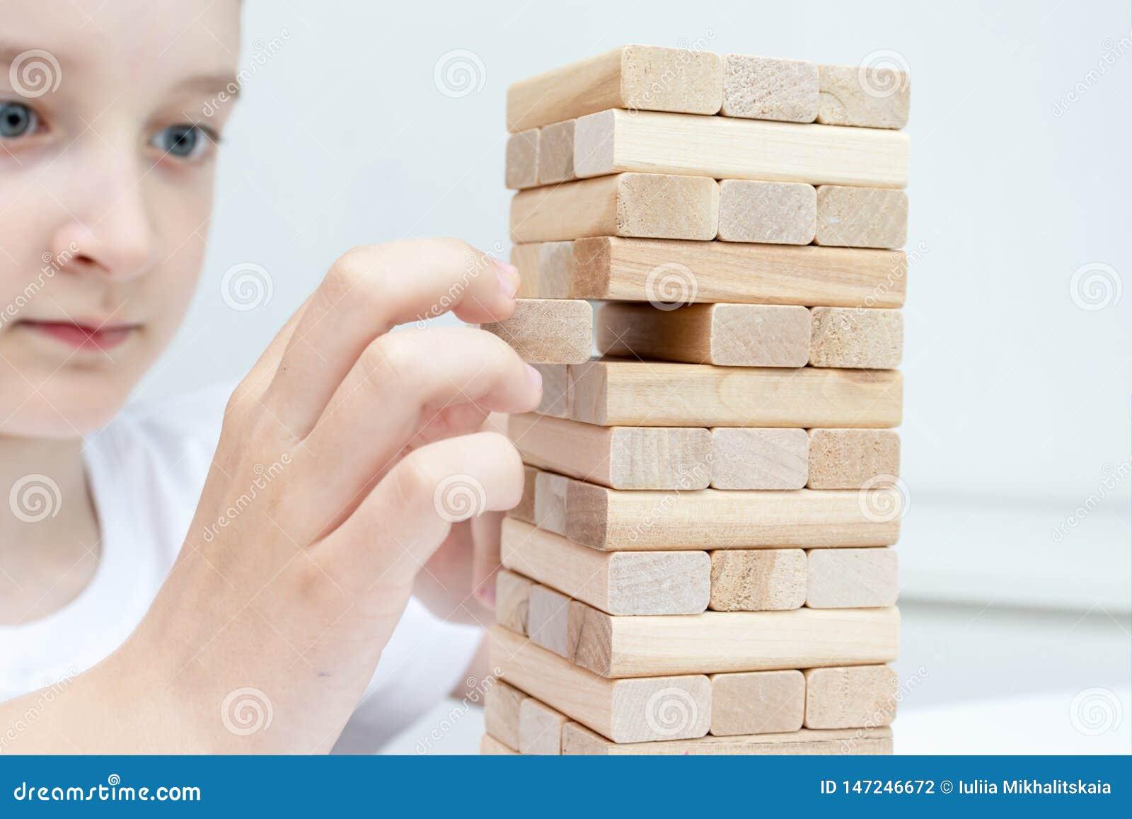 Preteen caucasian chłopiec bawić się drewnianą bloku wierza grę planszową dla ćwiczyć jego umysłową umiejętność i badanie lekarsk