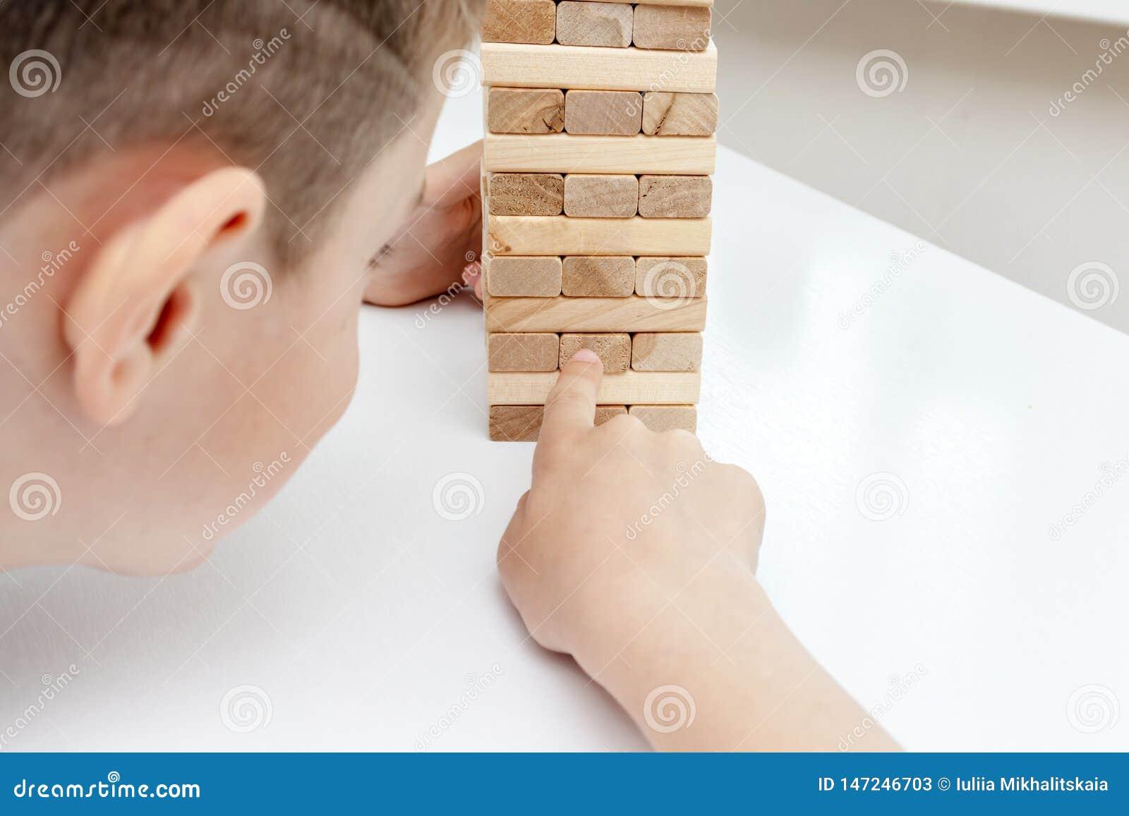 Preteen caucasian ch?opiec bawi? si? drewnian? bloku wierza gr? planszow? dla ?wiczy? jego umys?ow? umiej?tno?? i badanie lekarsk
