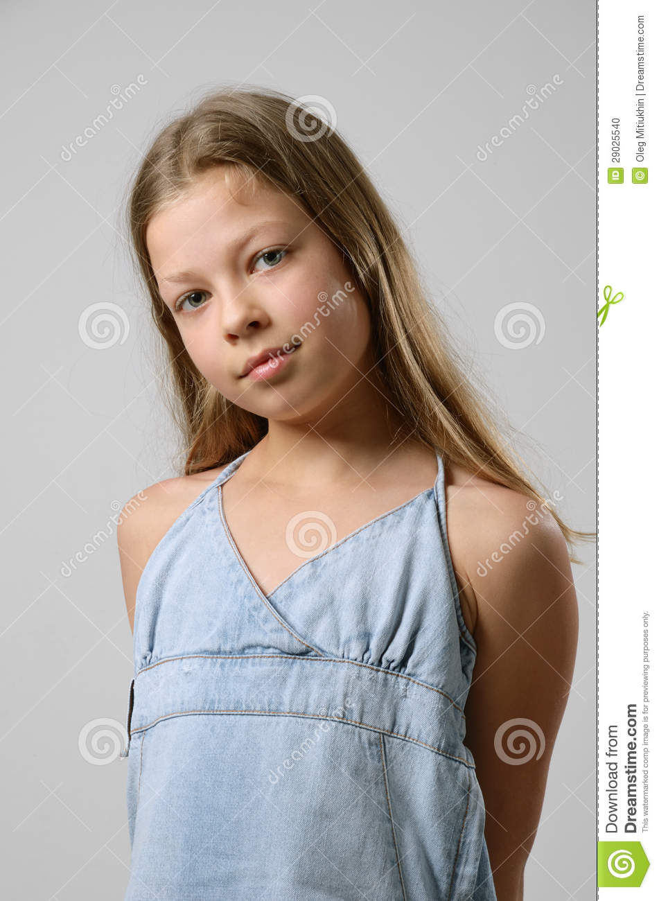 preteen girl is standing and looking at the camera. Her fair long ...