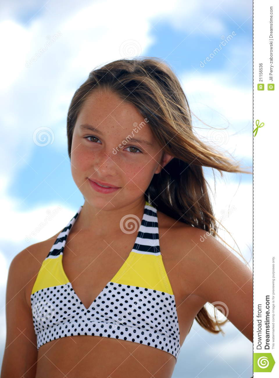 white preteen girl in a yellow white and black polka dot and striped