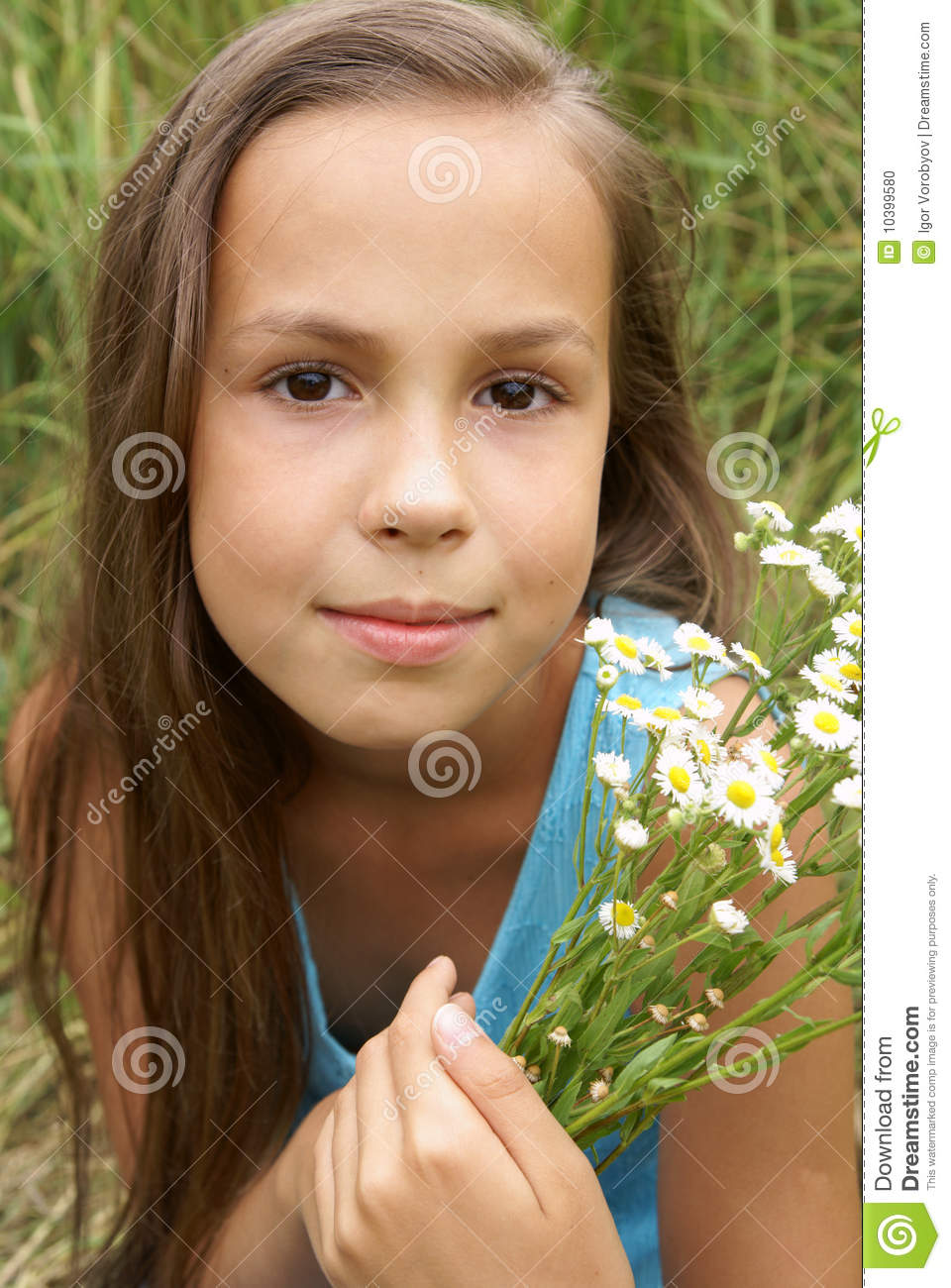 Beautiful preteen girl in blue dress with field flowers outdoors.