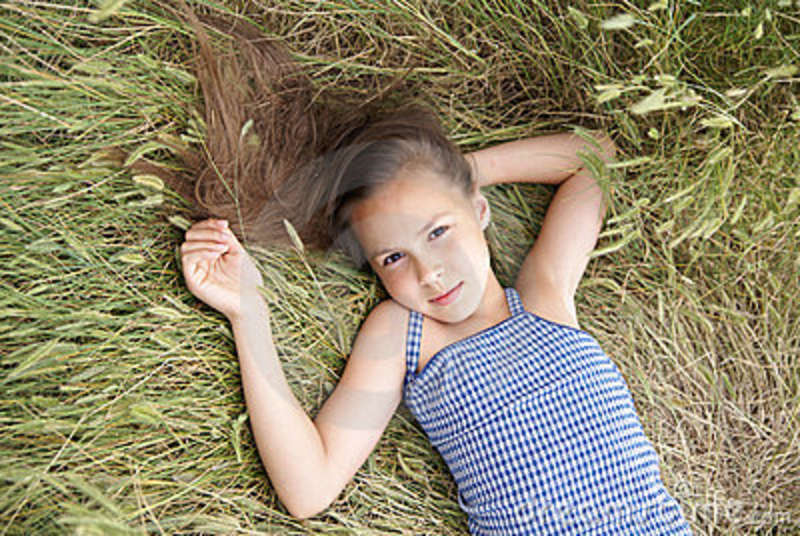 Preteen girl on grass background Stock photo and royalty