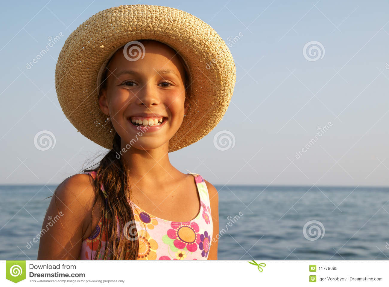 Preteen girl in straw hat enjoying sun-bath on sea beach.