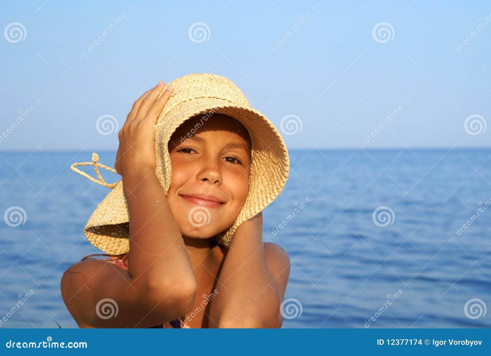 Preteen girl in straw hat enjoying sunbath on sea beach.