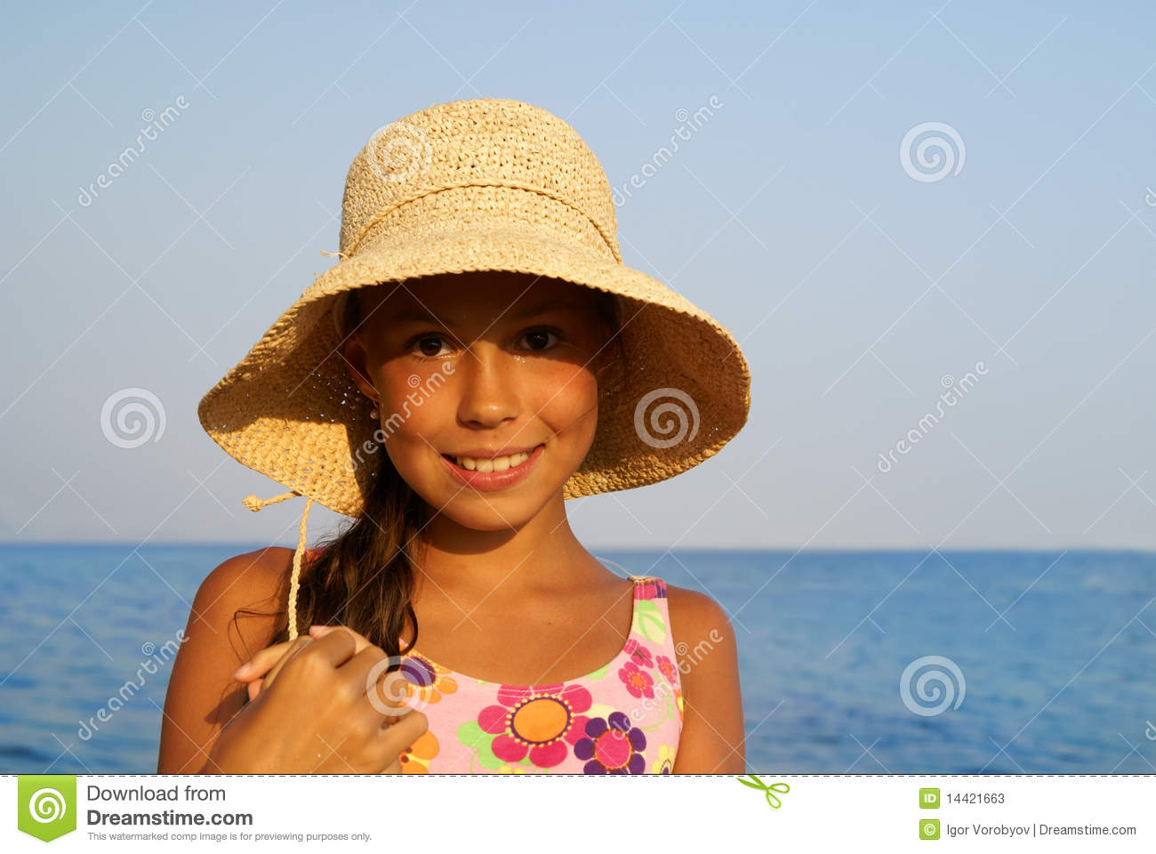 Cheerful preteen girl in straw hat enjoying sun-bath on sea beach.