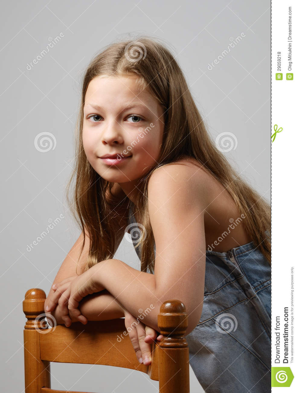 preteen girl is smiling and looking at the camera. Her fair long ...
