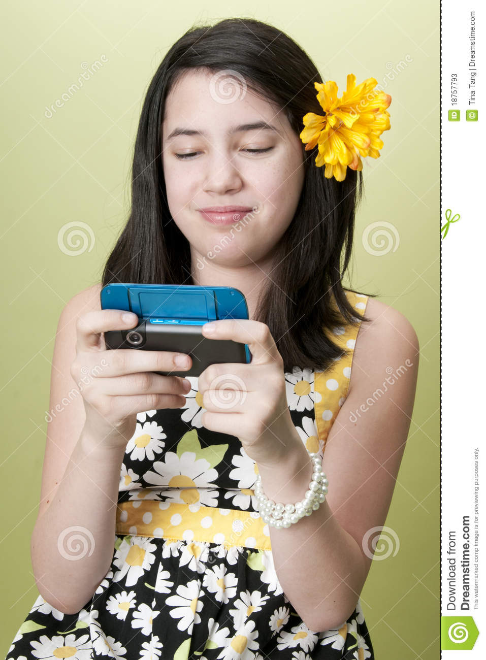 Preteen girl texting on cell phone.