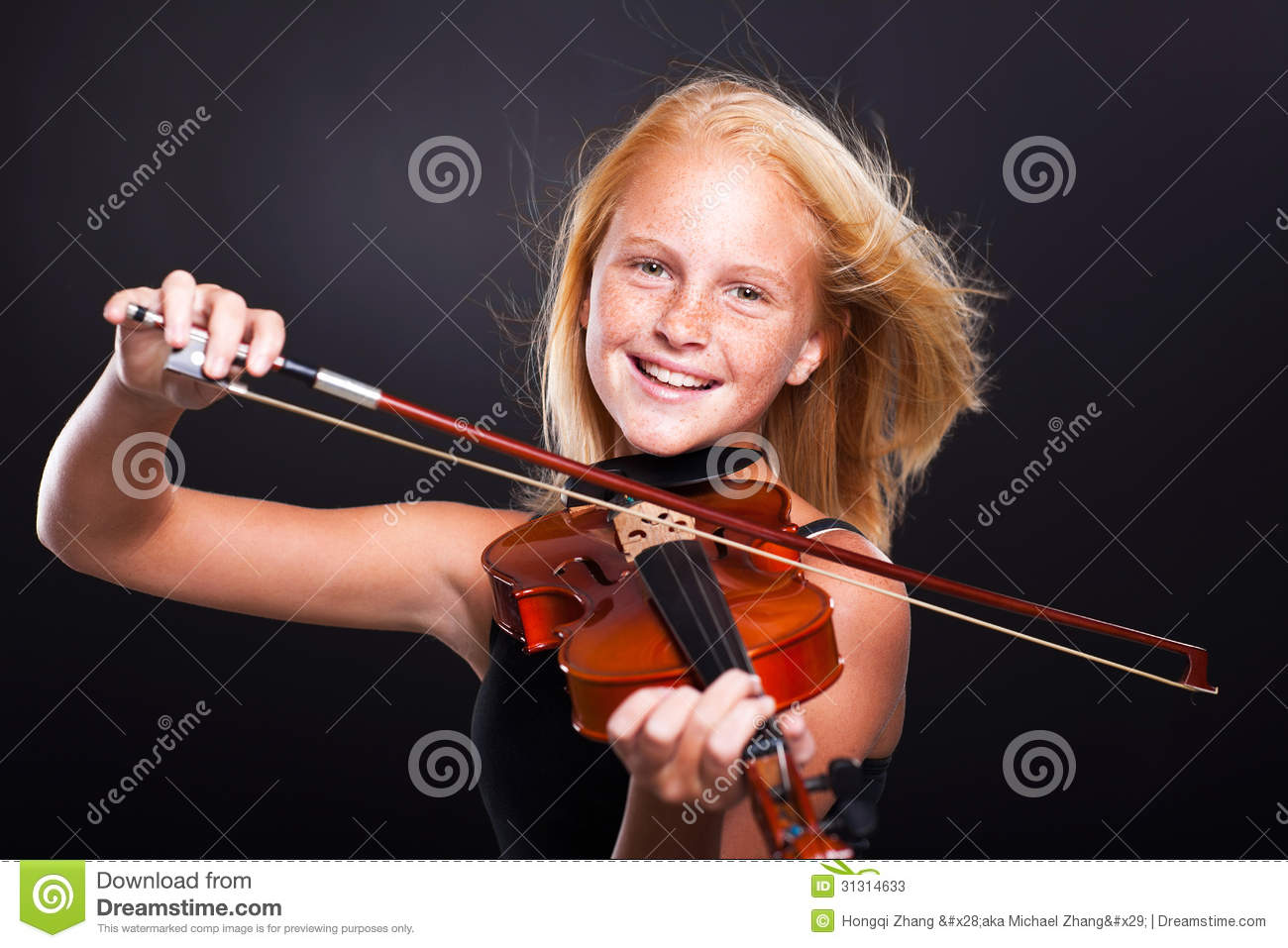 Cheerful preteen girl playing violin on black background.