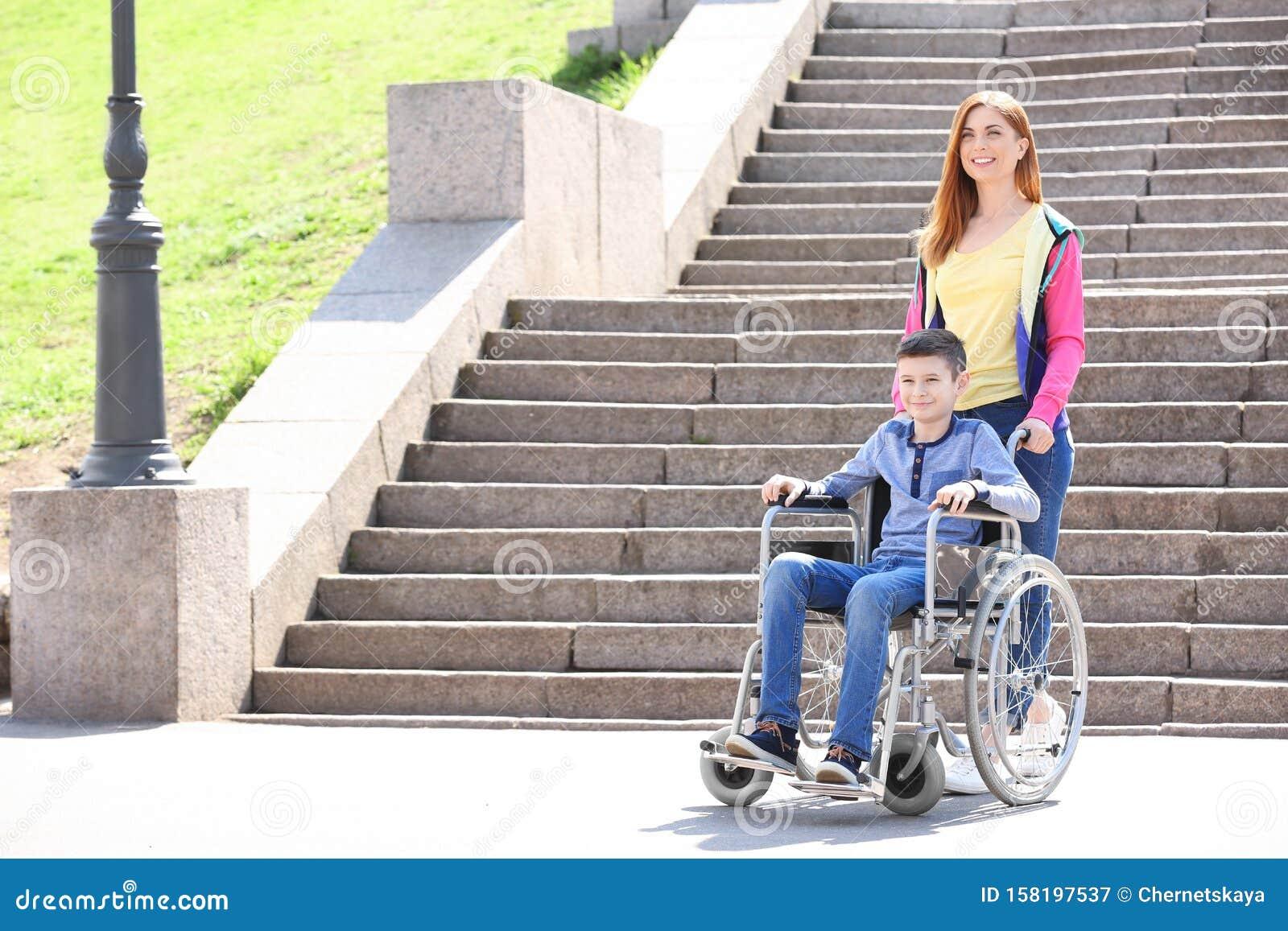 Preteen Junge Im Rollstuhl Mit Seiner Mutter Stockbild