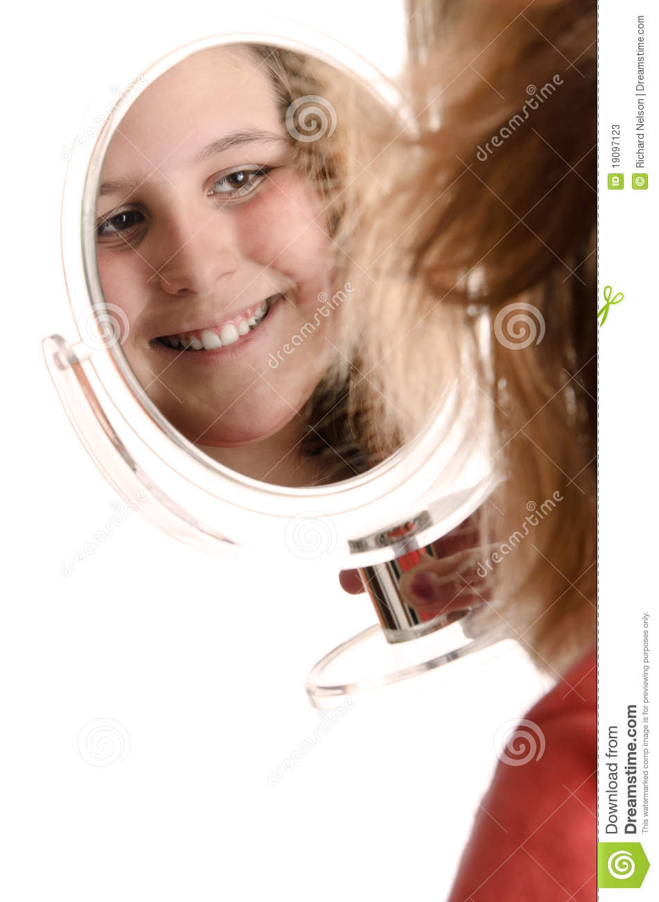 smiling preteen girl is looking at herself in a small mirror ...