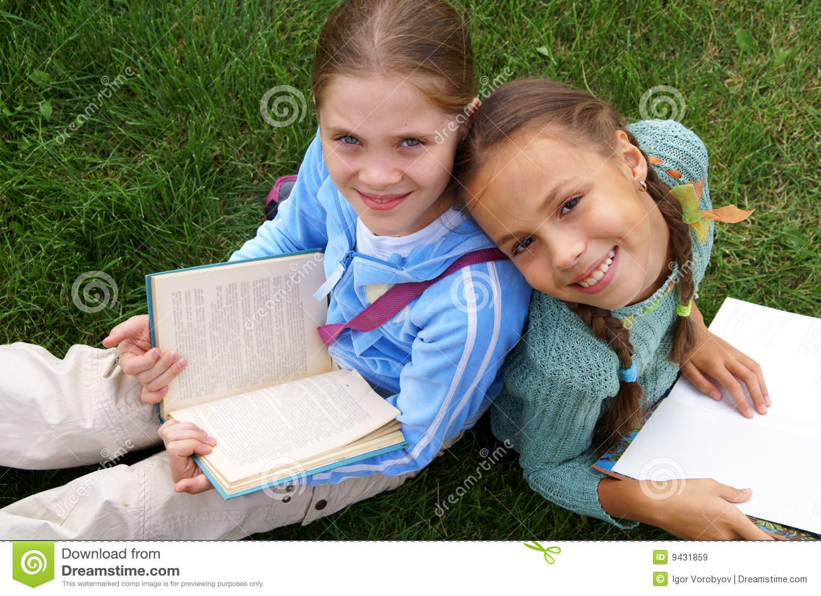 Preteen school girls reading books on green grass background outdoors.