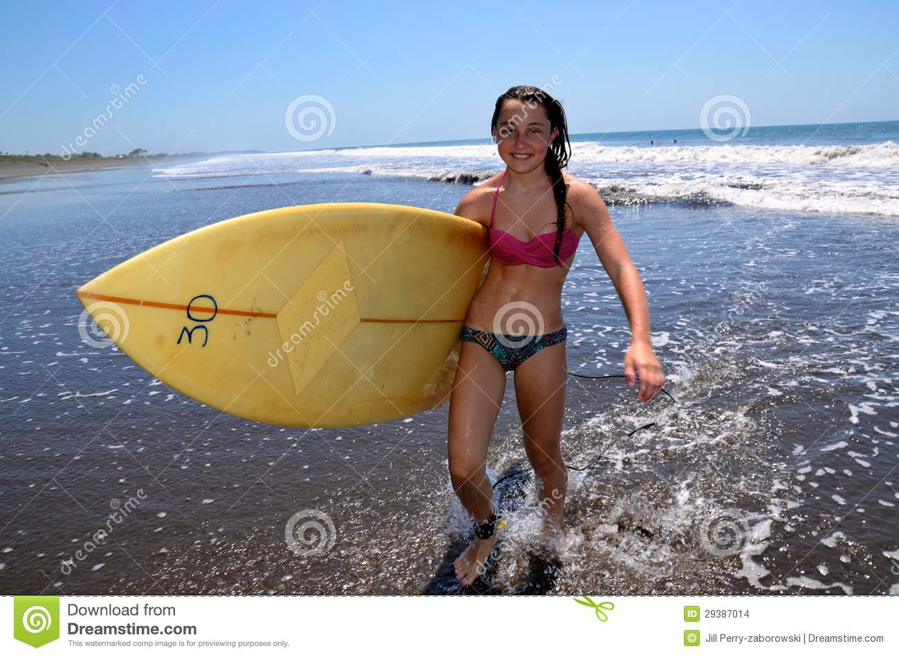 preteen caucasian surfer girl in bikini carrying surfboard out of ...