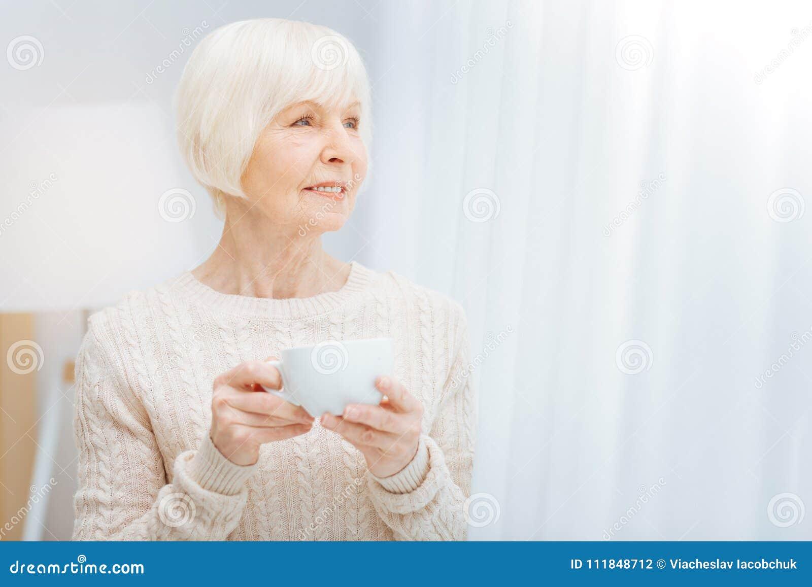 Prettig bejaarde die een kop houden en de afstand onderzoeken