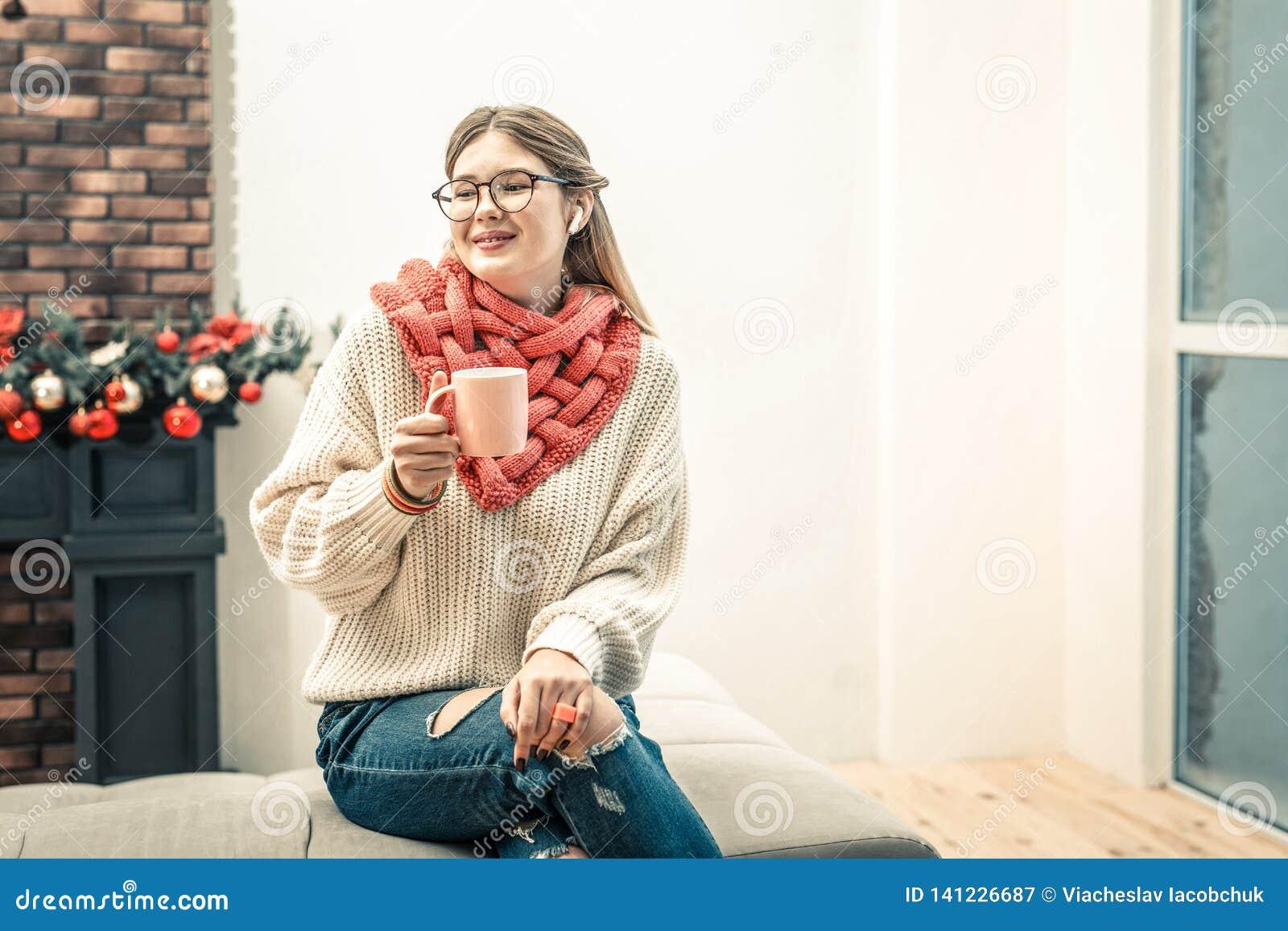 Prettige vrouwenzitting met gekruiste benen en het drinken hete koffie