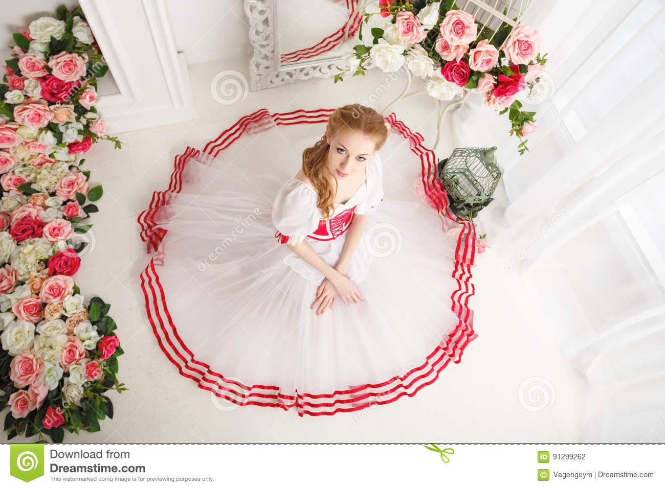 35781abc2863 A sweet ballerina in a scenic costume and bouquets of spring flowers. Retro  dress. She sits on the floor. High angle shooting
