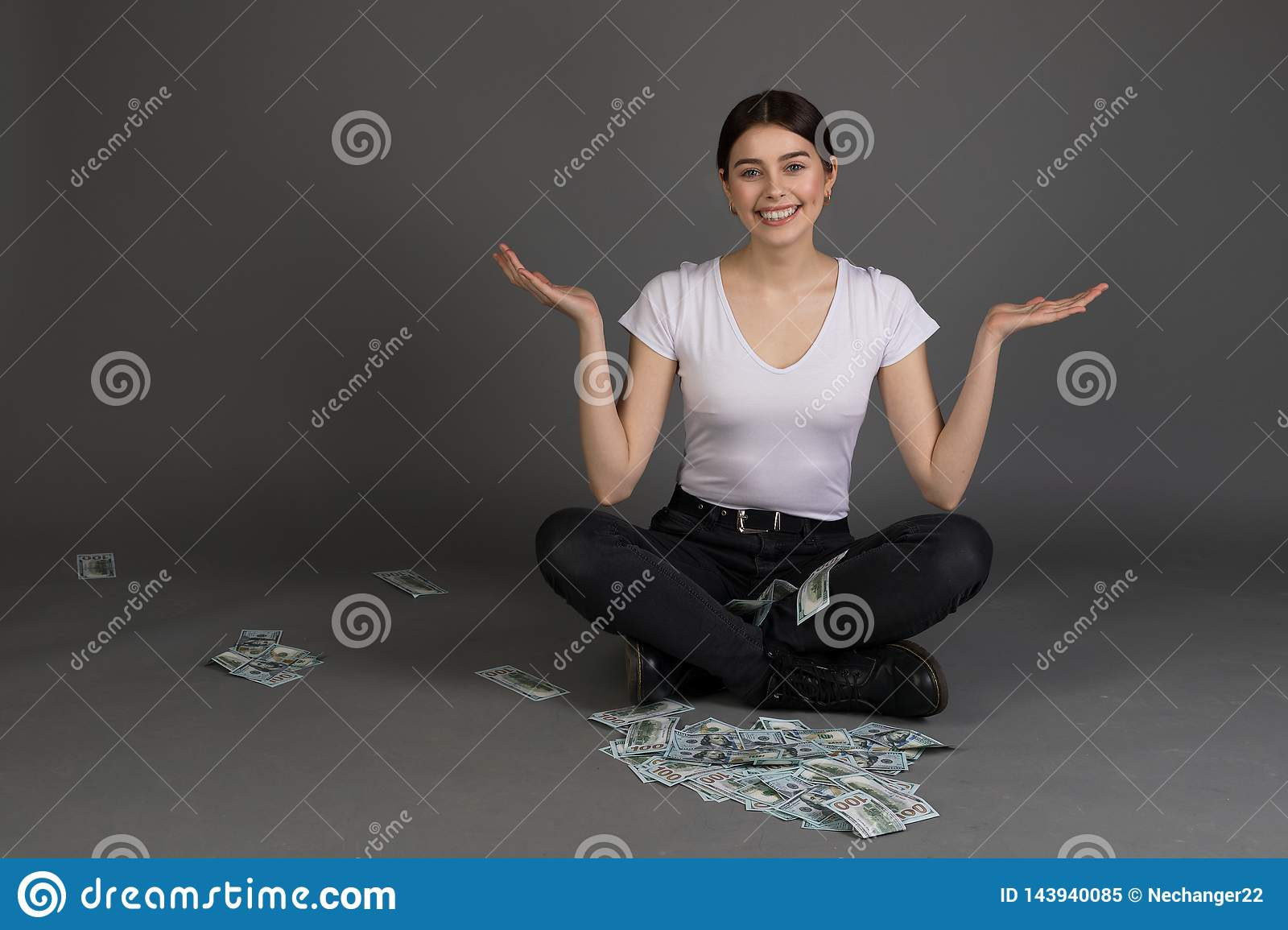Pretty beautiful girl with brunette hair looking at camera sitting in lotus position
