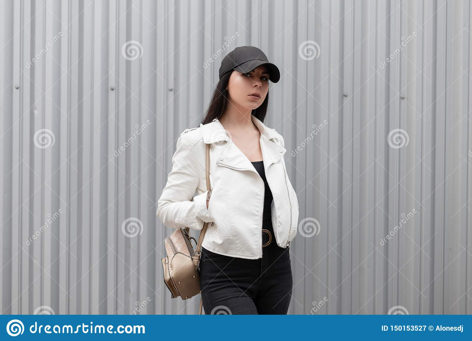 Pretty beautiful young woman with a stylish gold backpack in a fashionable white leather jacket in black jeans