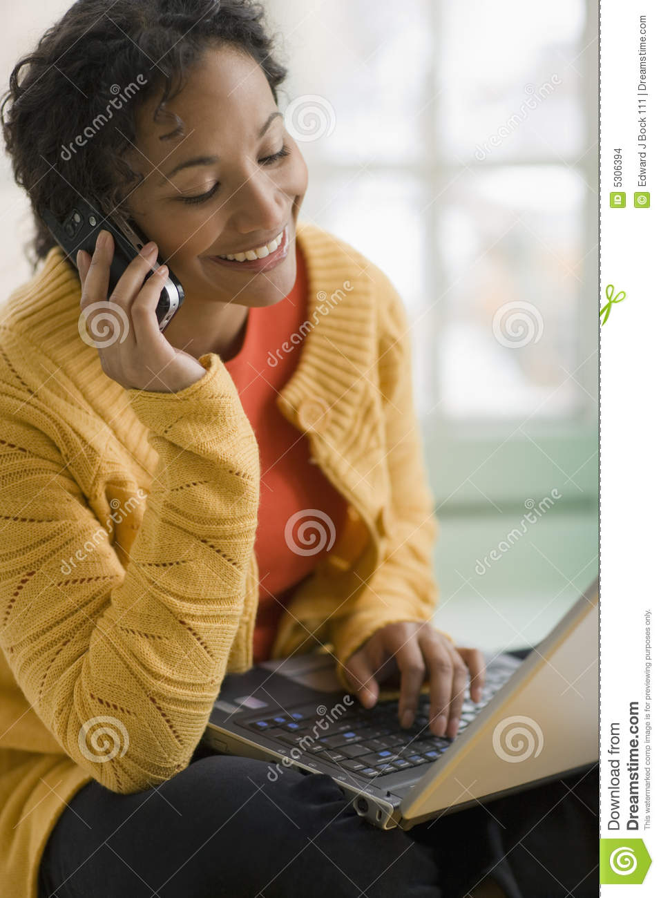 Pretty black woman on cell phone and laptop