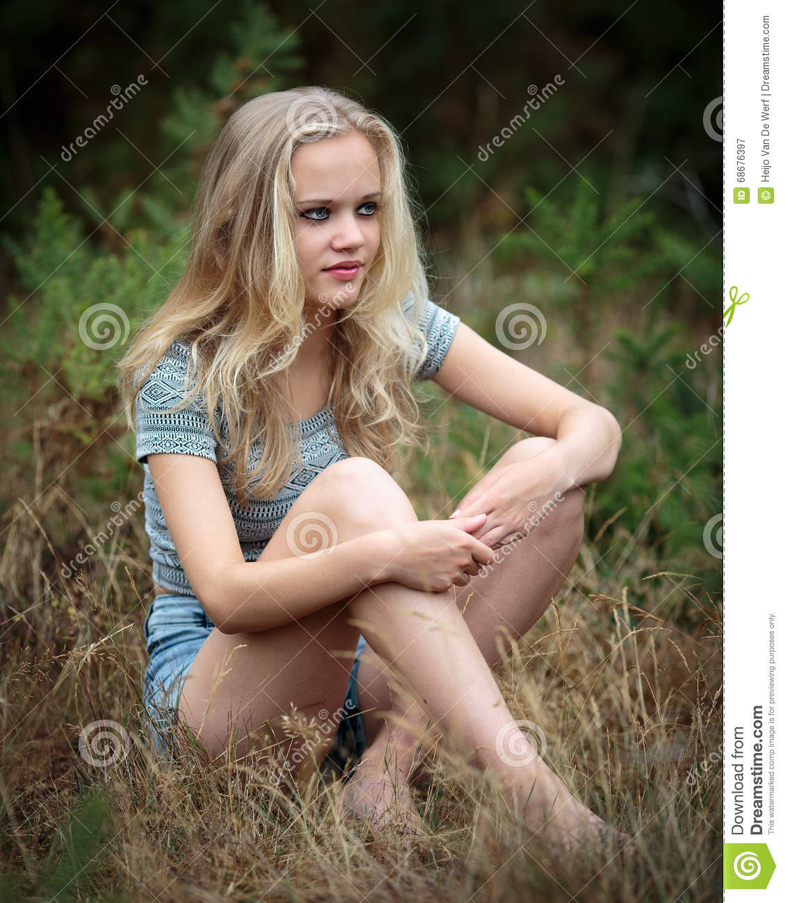 Pretty Blond Teenager Sitting In The Grass Stock Image