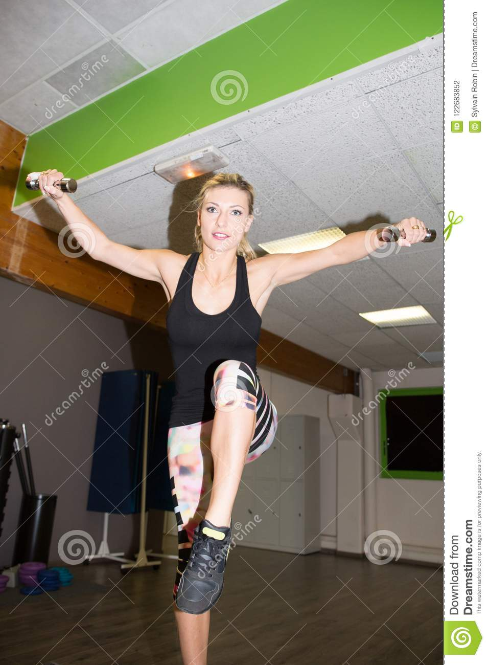 blonde beauty young woman in gym working out with pair of dumbbells in health and fitness concept