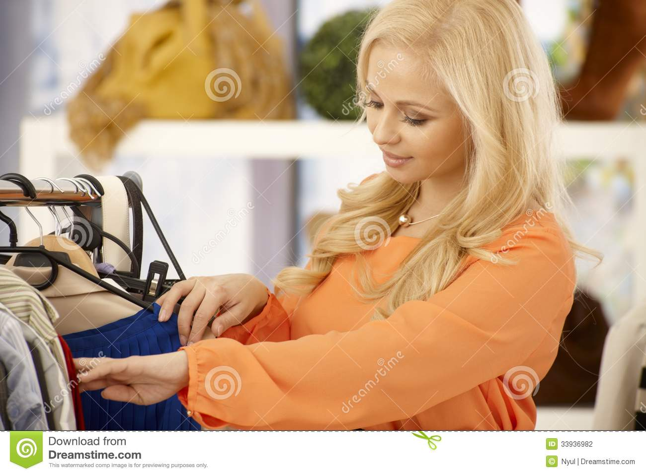 Pretty blonde woman searching among clothes at clothes store
