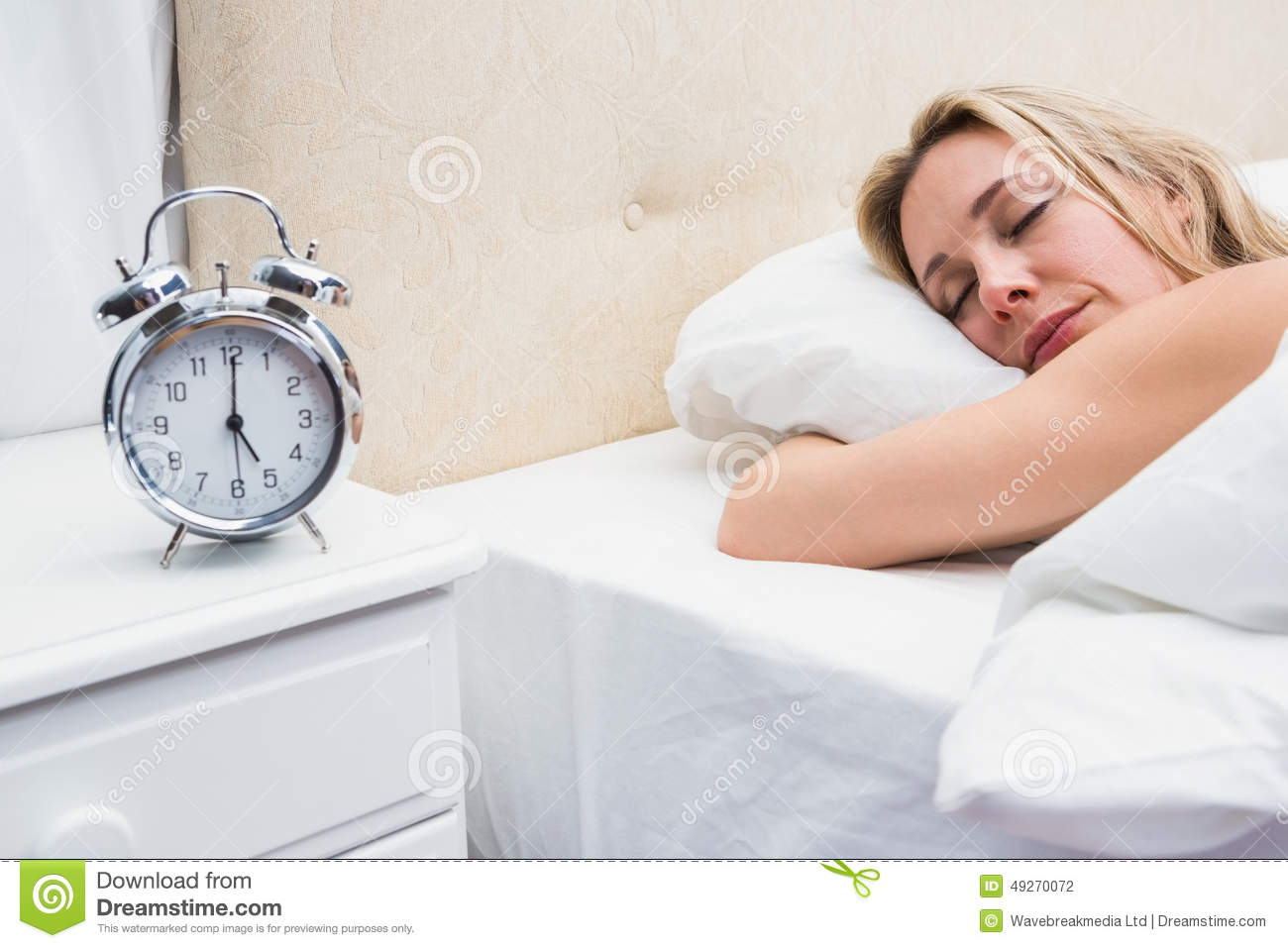 Pretty Blonde Sleeping In Bed With Alarm Clock Stock Photo