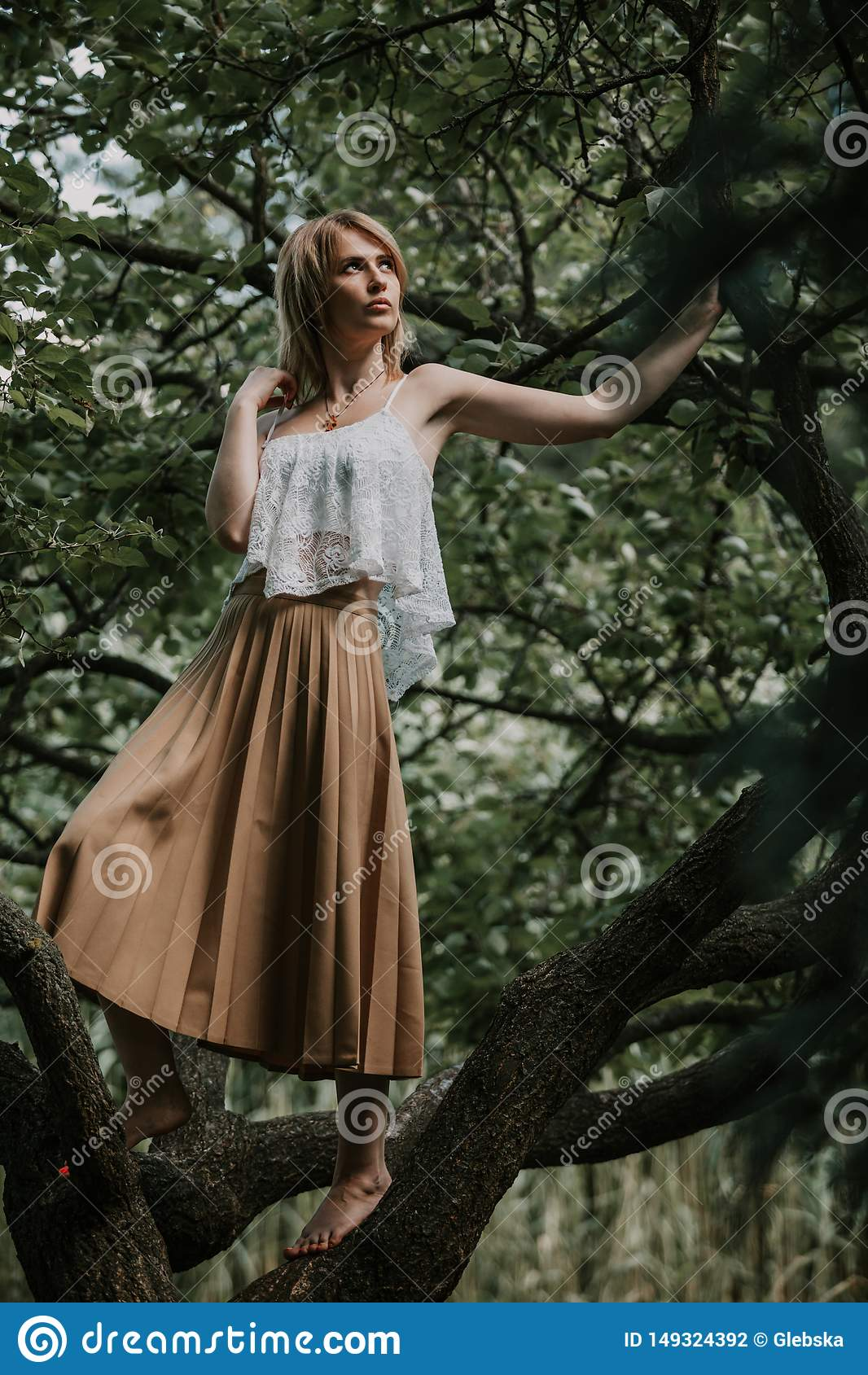 https://thumbs.dreamstime.com/z/pretty-blonde-stands-barefoot-tree-branch-portrait-nature-slender-girl-white-top-skirt-standing-summer-day-149324392.jpg