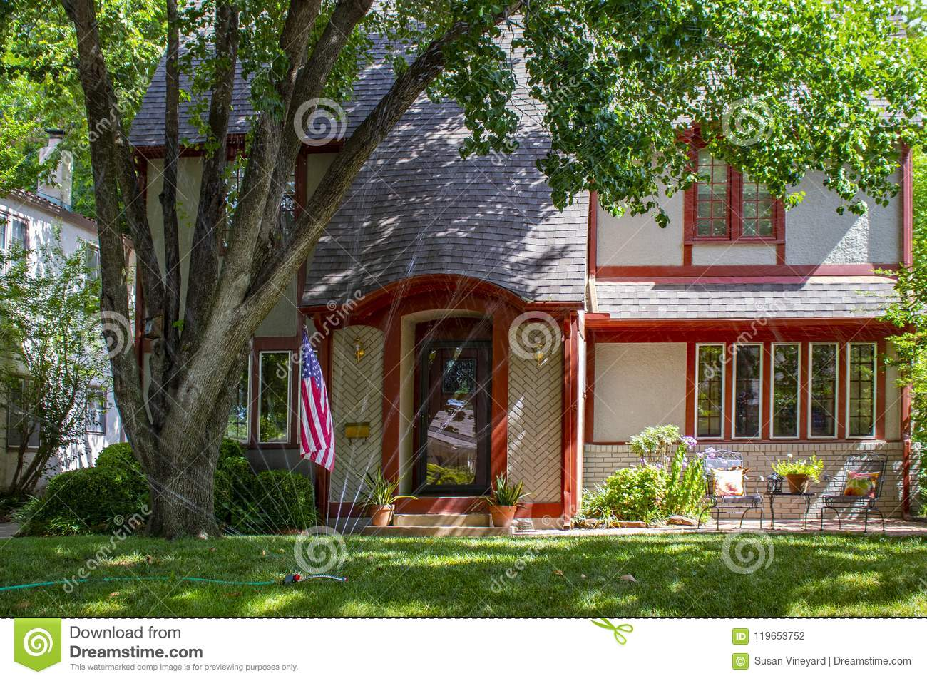 A Pretty brick house trimmed in red with patio and flowers and big trees displaying American flag with watering sprinklers on grass lawn & Pretty Brick House Trimmed In Red With Patio And Flowers And Big ...