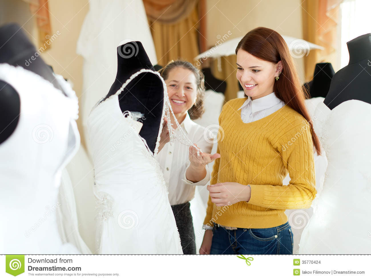 Wedding Photography Consultant: Pretty Bride Chooses Bridal Outfit At Wedding Store Stock