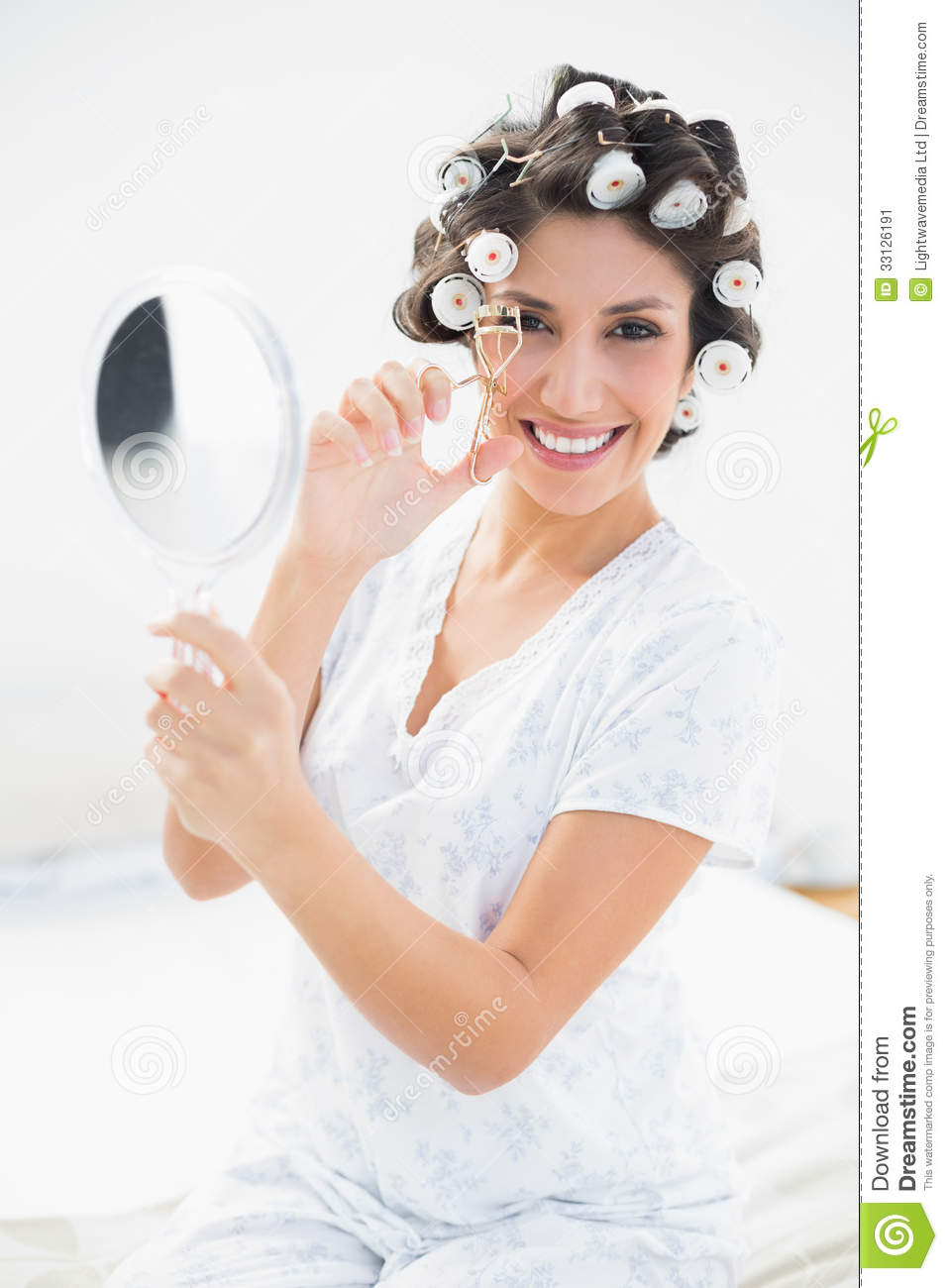 Pretty Brunette In Hair Rollers Holding Hand Mirror And