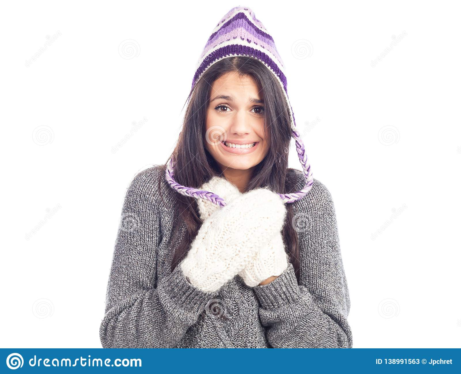 Pretty brunette woman with a woolen Peruvian hat a sweater and gloves has cold