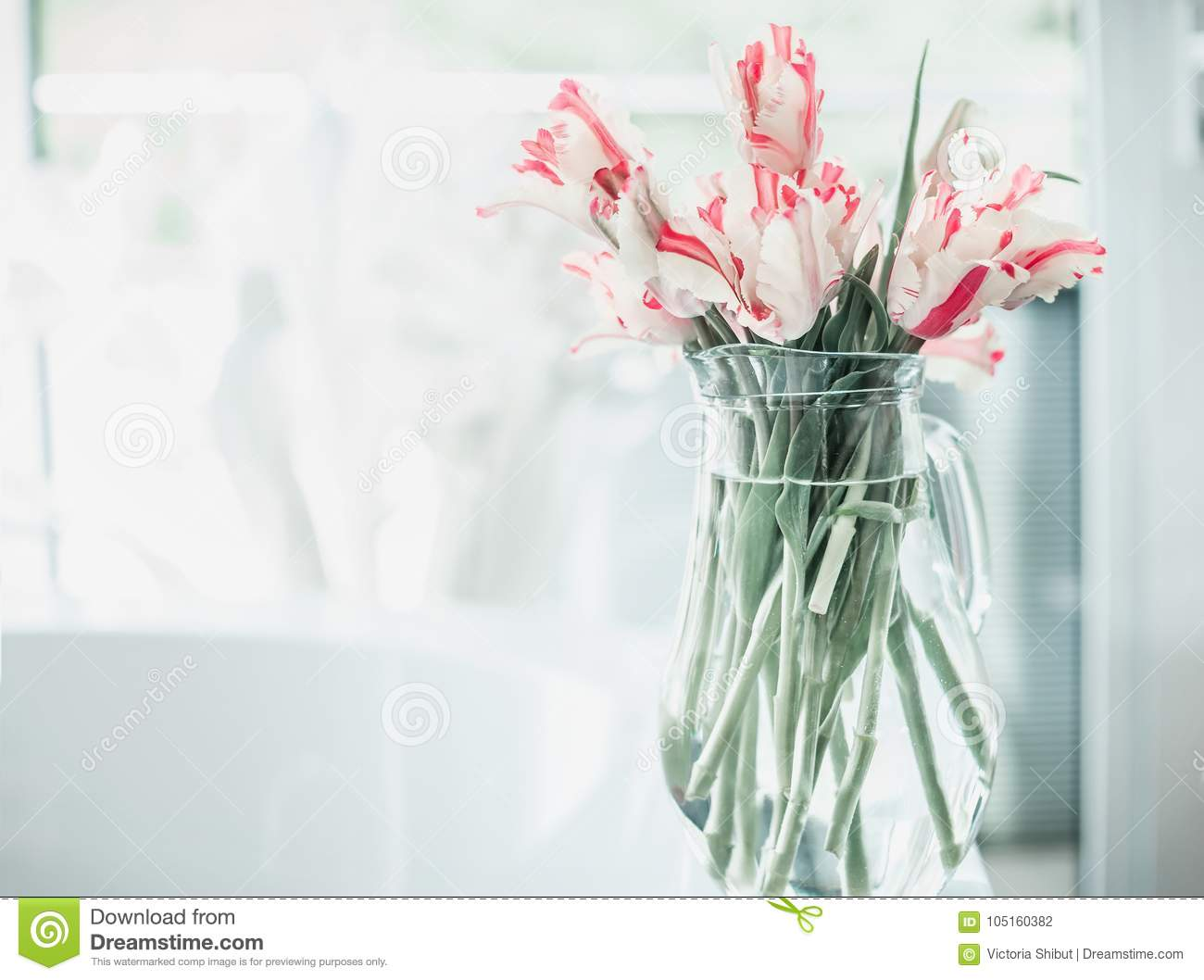 Pretty Bunch Of Tulips In Glass Jug On White Table At Window