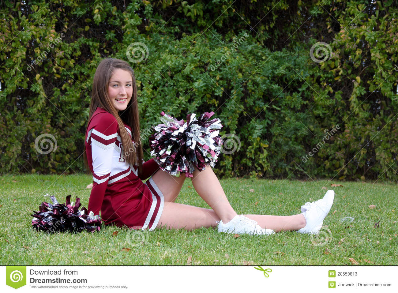 Pretty young cheerleader wearing a maroon colored uniform and pompoms ...