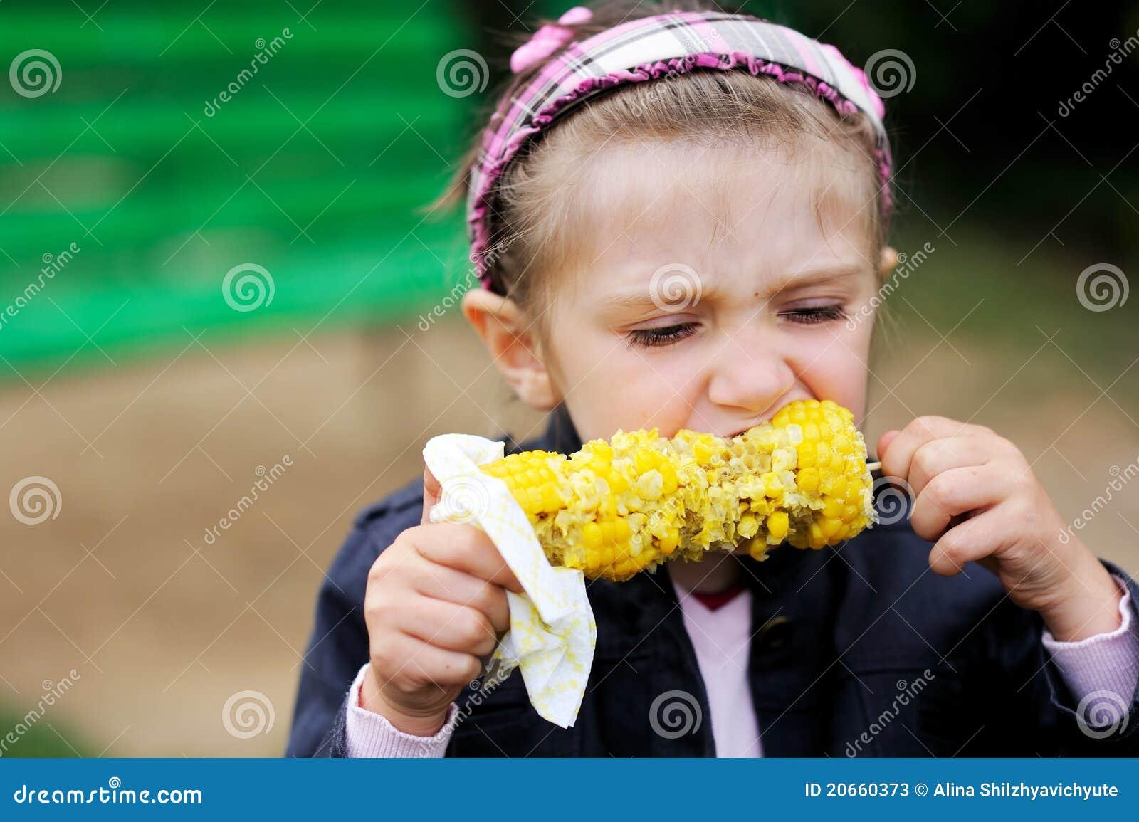 Pretty child girl eats a boiled corn