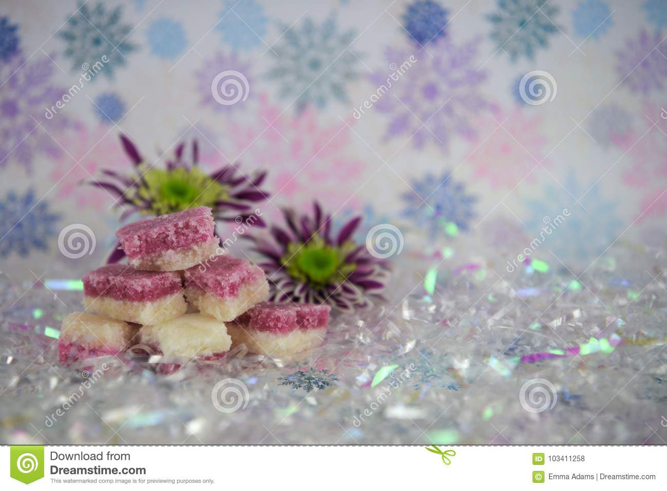 Pretty christmas food photography picture of english old fashioned coconut ice treats on pastel colour glitter snowflake pattern wrapping paper background and shiny shimmer gift wrap and with english winter flowers mightylinksfo
