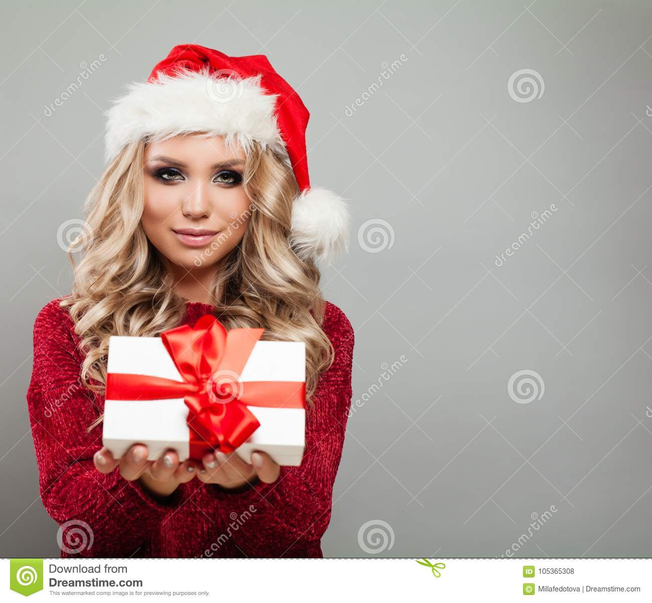 14e2a6f2c0a3b Pretty Christmas Model Holding White Christmas Gift Box with Red Ribbon.  Cute Woman in Santa Hat on Gray Background with Copy space