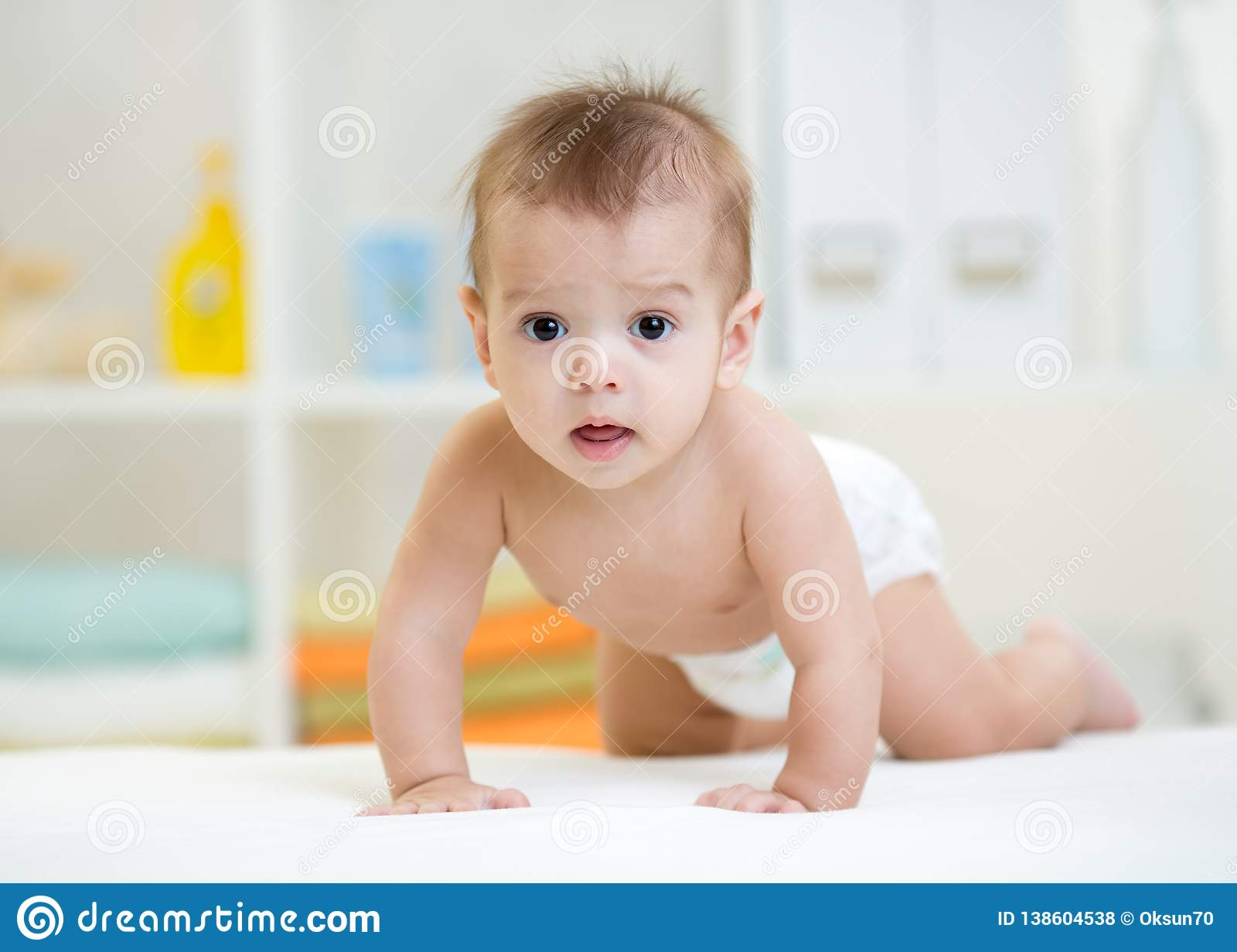 Pretty crawling caucasian baby werared diaper indoor