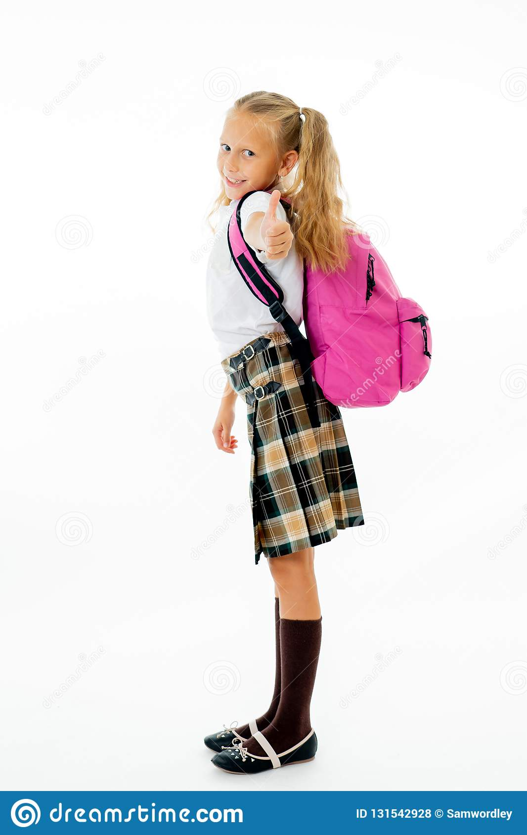 Pretty cute blonde hair girl with a pink schoolbag looking at camera showing thumb up gesture happy to go to school isolated on