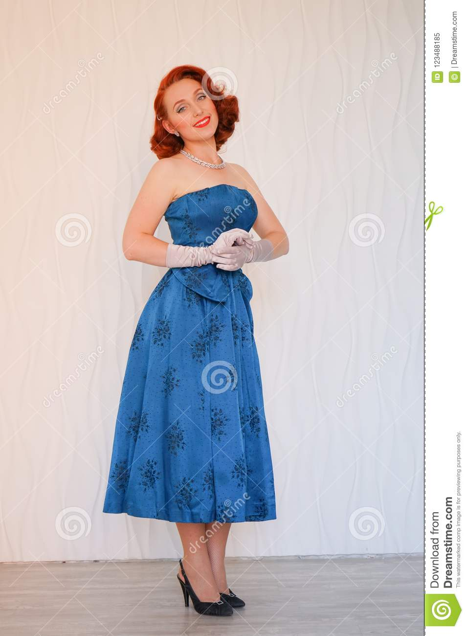 Beautiful pin up woman standing in blue dress against white wall in empty room and smiling