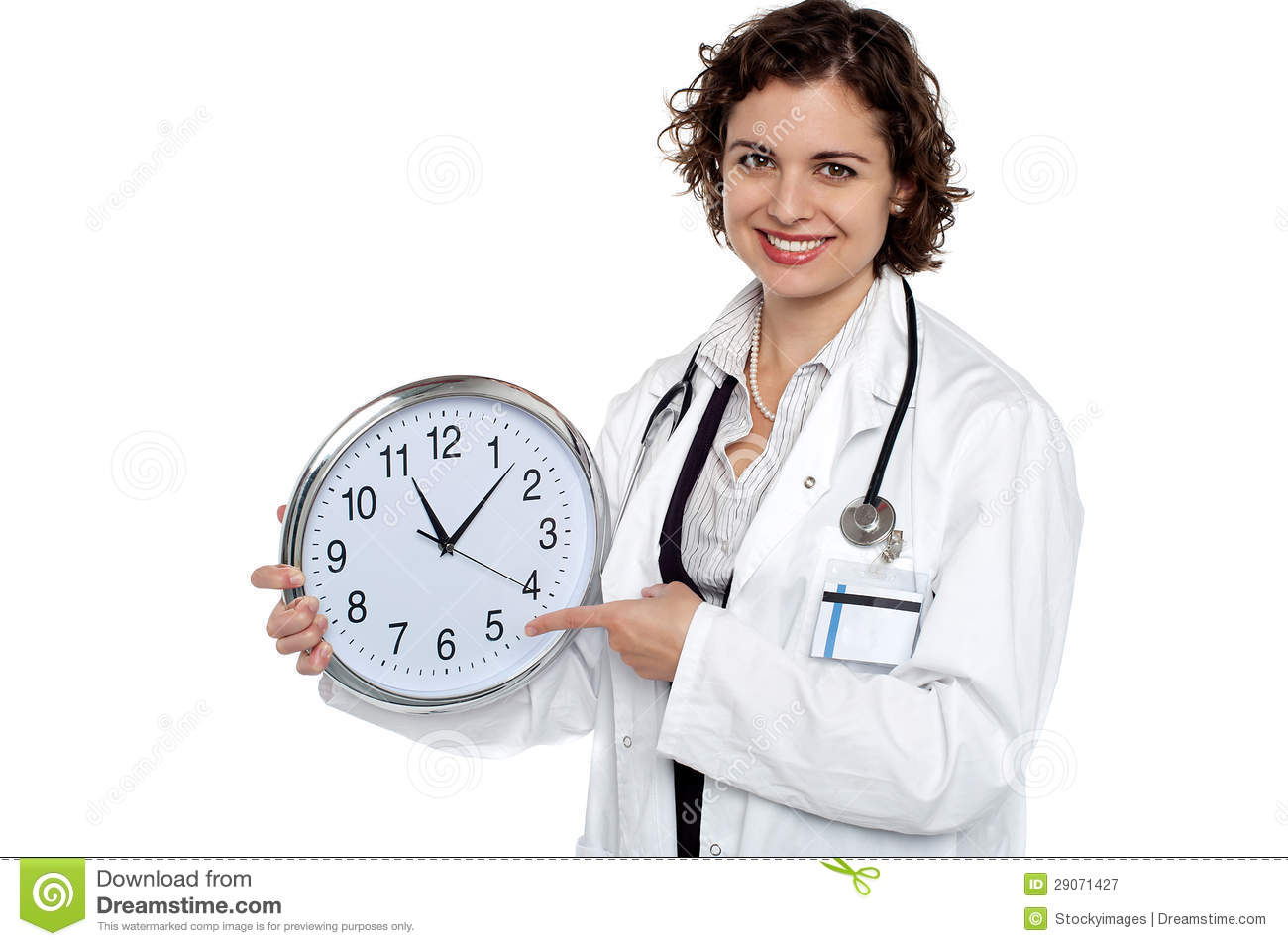 Pretty Doctor Pointing Out Time On Wall Clock Stock Image