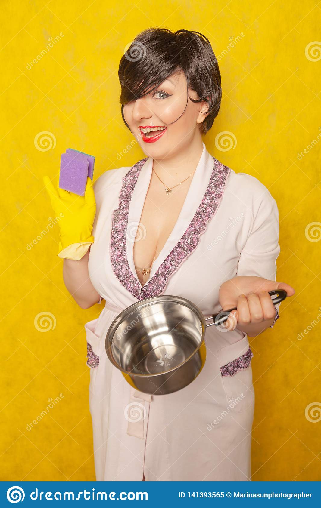 Beautiful bright brunette in a Bathrobe holds a pan and a sponge for washing dishes. young woman housewife on yellow studio backgr