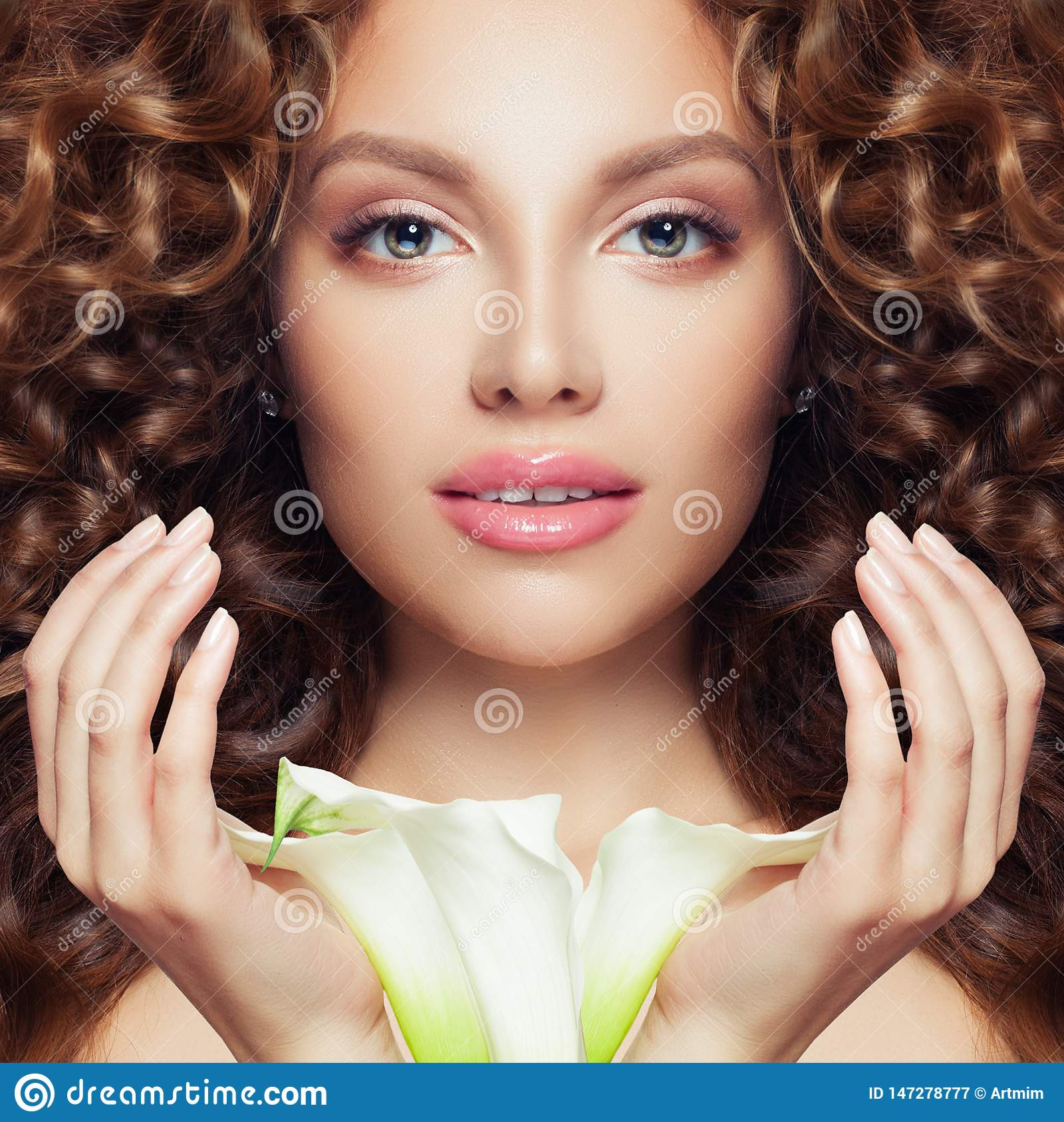 Pretty face. Perfect model woman with curly hair, clear skin and flower