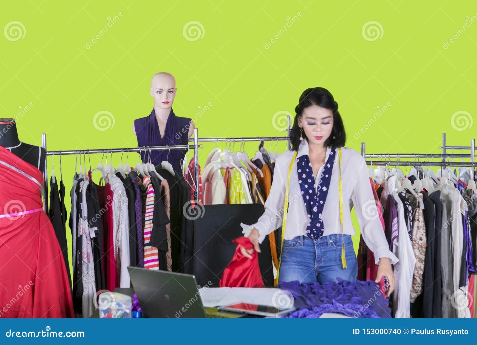 Pretty fashion designer checking a fabric on studio