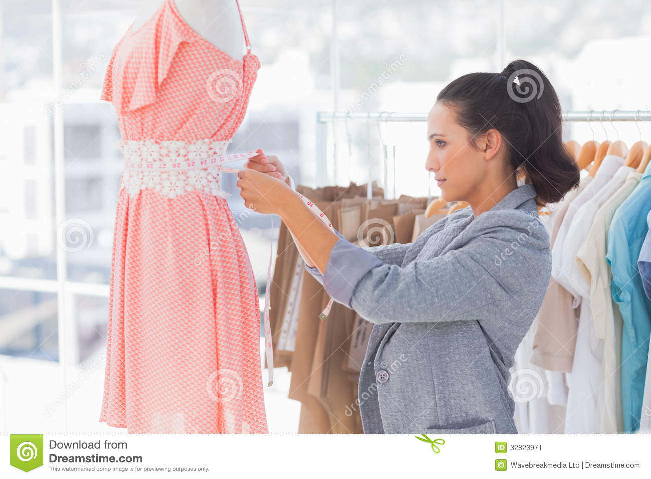 Pretty fashion designer measuring dress on a mannequin Contemporary fashion designers