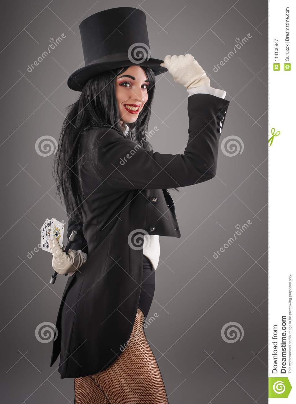 Female magician in performer suit with magic wand and playing ca