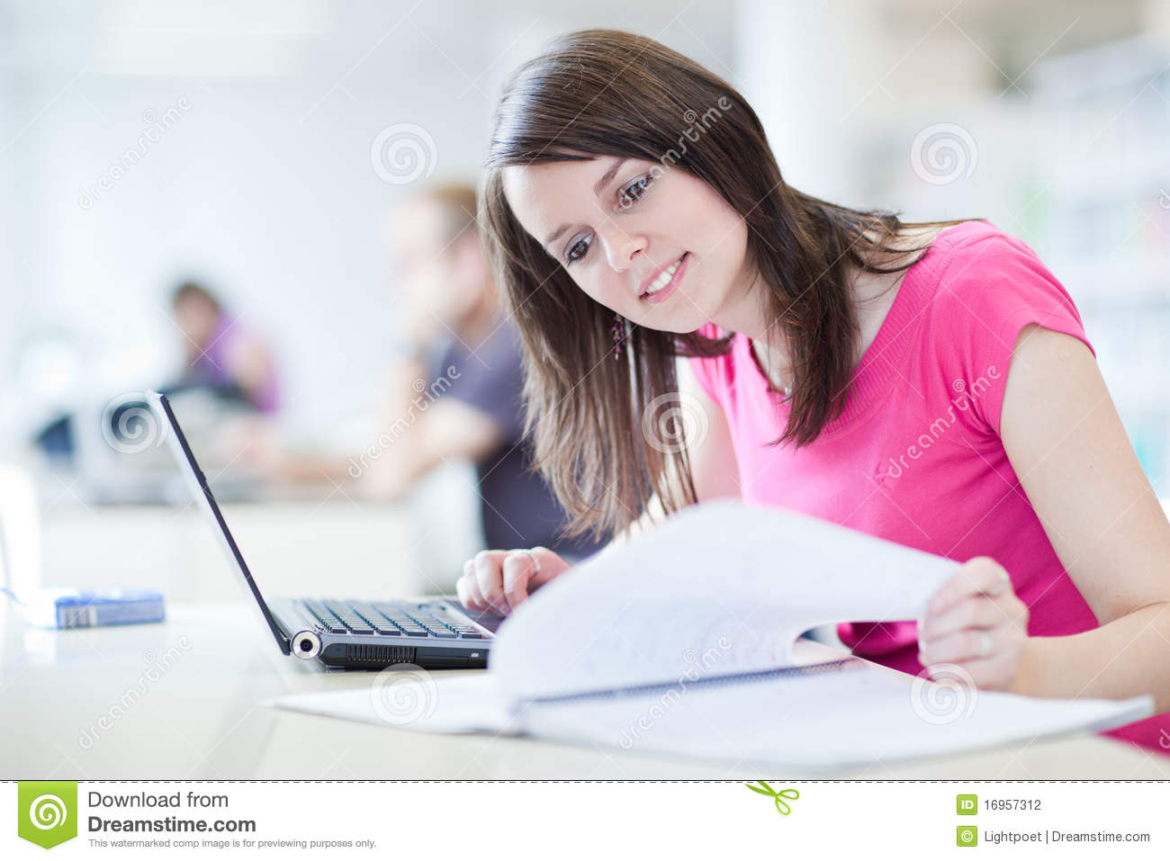 Pretty female student with laptop and books