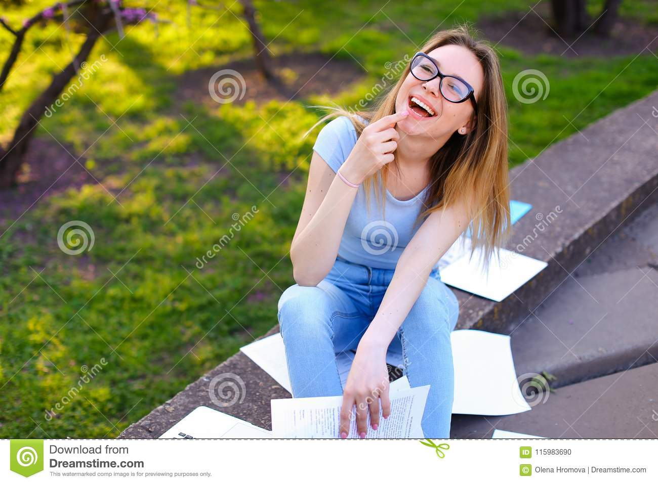Pretty female student reading papers, smiling and studying in spring park.